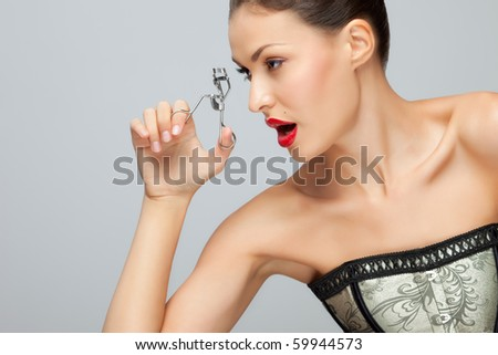 Brutal make-up. A pretty young woman holding an eyelash curler in her hand. - stock photo