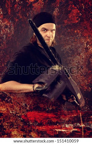 brutal man holding a chainsaw and a slight smile  - stock photo