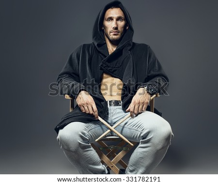 Brutal man in a hood with drumsticks