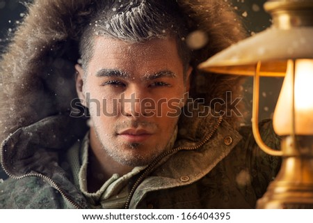 Brutal man walking under snowstorm at night lighting his way with lantern - stock photo