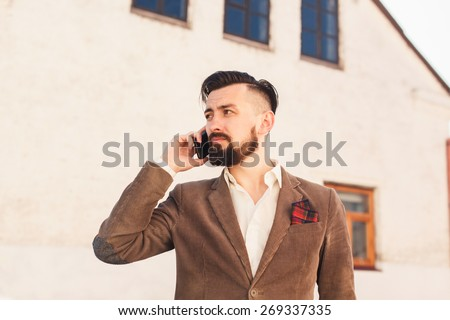 brutal man with a mustache and beard with a fashionable haircut posing on the street in a brown suit and talking on the phone - stock photo