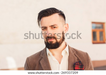 brutal man with a mustache and beard with a fashionable haircut posing on the street in the brown suit