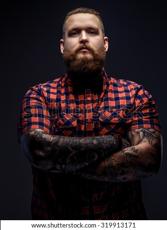 Brutal man with beard and tattooes on his arms. - stock photo