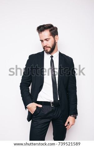 brutal man young brunette in a business suit posing in Studio on a white background. bushy beard on the face and clean skin. emotional portrait. the concept of a successful entrepreneur or Manager