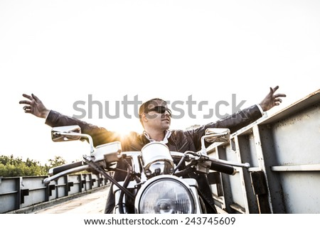 Brutal portrait biker man in sunglasses sit on chopper motor bike on sunset sky Stand old rusty metal bridge in city against house and sunny heaven background Empty copy space for inscription Hands up - stock photo