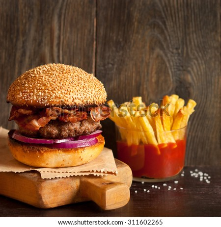 Brutal smoked bacon hamburger on wooden cutting board and fried potatoes with tomato sauce. - stock photo