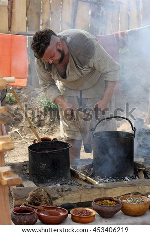 "BRYANSK, RUSSIA - July 16, 2016: people in Ancient clothes the kindle with the bellows the fire in the hearth.He dyes cloth. Around the smoke and ash. A male participant of the festival ""old Bryansk""."
