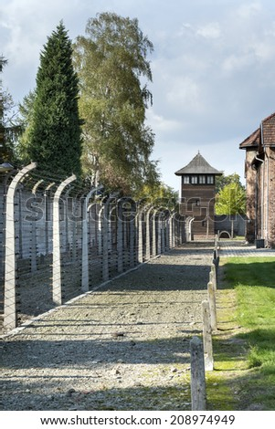 BRZEZINKA, POLAND - OCTOBER 13, 2012: Outdoor Walkway Lined With Electrified Barbed Wire in Auschwitz Camp II. Auschwitz was a network of concentration and extermination camps built by Nazi Germany. - stock photo