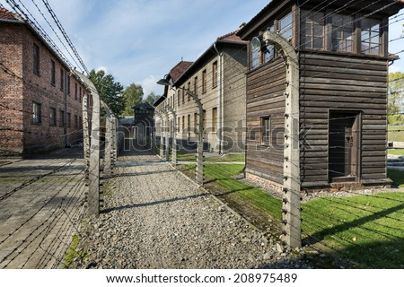 BRZEZINKA, POLAND - OCTOBER 13, 2012: Outdoor Walkway Lined With Electrified Barbed Wire in Auschwitz Camp II. Auschwitz was a network of concentration campus built n Polland by Nazi Germany.  - stock photo