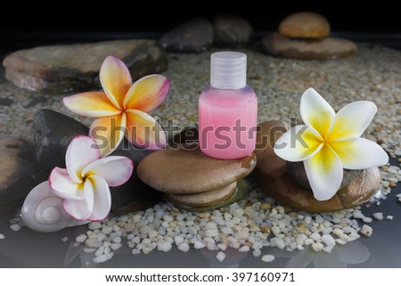Bubble bath and shower gel liquid with flower plumeria or frangipani on pebble rock and water - stock photo