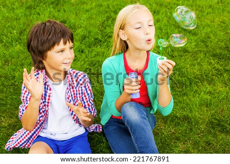 Bubble fun. Two cute little children blowing soap bubbles while sitting on the green grass together - stock photo