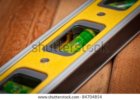 Bubble level on a wooden boards background - stock photo