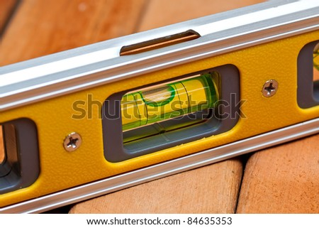 Bubble level on wooden boards - stock photo