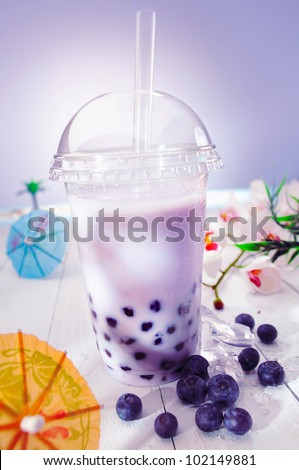 Bubble tea blended with milk and black currant berries and purple boba or pearls - stock photo