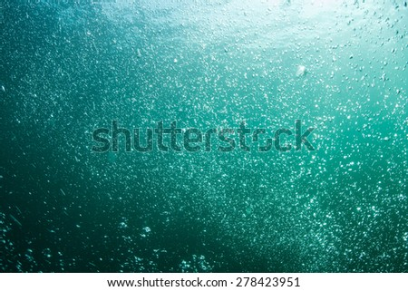 Bubbles of gas rise from scuba divers who explore the seafloor of the northern Atlantic Ocean. - stock photo