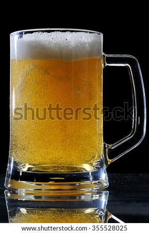 Bubbles on brown full beer glass on black - stock photo