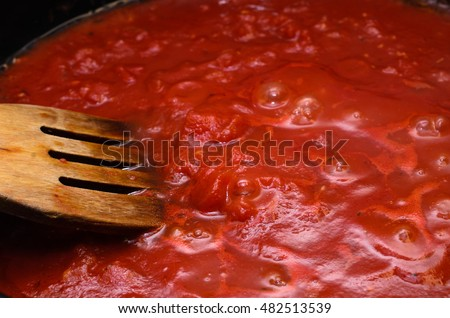 Bubbling hot tomato sauce for pasta, cooking in pan with wooden spatula.
