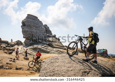 Bucegi Mountains, Romania July 09, 2015: Unidentified group of bikers climbs the hill in Bucegi Mountains in Romania on July 09, 2015.  - stock photo