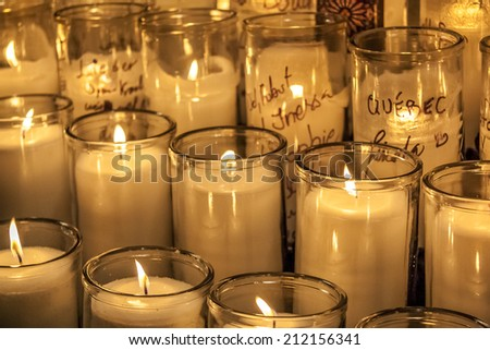 Buch of big candles burning at a catholic church symbolizing religion and God Fearing. - stock photo