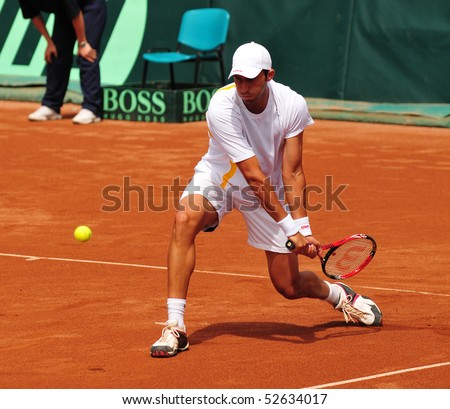 BUCHAREST, ROMAINIA  MAY 8:  Romania's Horia Tecau performs a backhand during the Davis Cup doubles match between Romania and Ukraine at the BNR Arenas on May 8, 2010 in Bucharest, Romania. - stock photo