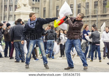 BUCHAREST, ROMANIA - APRIL 5: Unidentified men have fun and fight with white pillows on International Pillow Fight Day on April 5, 2014 in University Square, Bucharest, Romania.