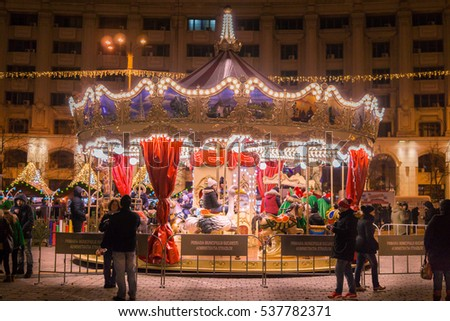 BUCHAREST, ROMANIA - DECEMBER 17, 2016: Merry-Go-Round (carousel) illuminated at night. Bucharest City At Night In front of the Parliament House, the second largest building in the world