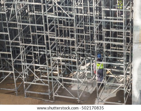 Bucharest, Romania, 15  February 2016: A worker walks through a scaffolding structure at the construction site of a building in Bucharest.