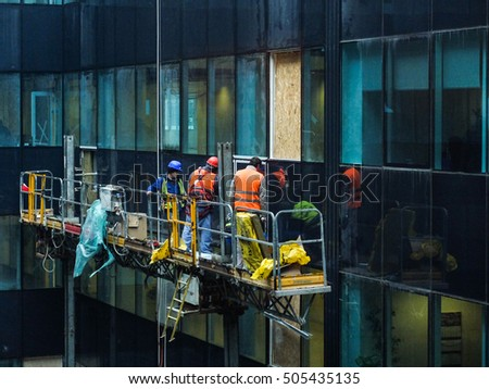 Bucharest, Romania, 1 February 2016: Laborers are mounting windows on a building in a construction site in Bucharest.