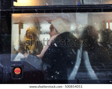 Bucharest, Romania, 4 January 2016: People are seen in a bus through a steamed window, during snowfall in Bucharest.