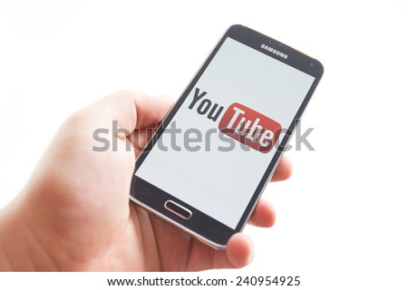 Bucharest, Romania - January 1st, 2015: Man holding brand new black Samsung Galaxy S5. YouTube is a video-sharing website headquartered in San Bruno, California. - stock photo