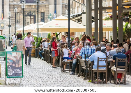 BUCHAREST, ROMANIA - JULY 04, 2014: Tourists Having Lunch At Outdoor Restaurant Downtown Lipscani Street. Lipscani is one of the most busiest streets of central Bucharest. - stock photo
