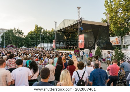 BUCHAREST, ROMANIA - JUNE 28, 2014: Crowd Of People Watching Free Classical Music Concert At Bucharest Music Film Festival In George Enescu Square Near The Romanian Athenaeum. - stock photo