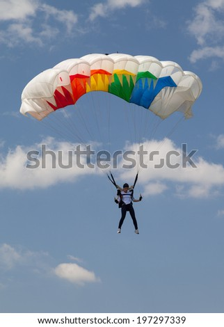 BUCHAREST, ROMANIA - JUNE 07, 2014: Paratrooper girl descending in the competition Red Bull Smaranda Order, dedicated exclusively to women. Smaranda Braescu is the first woman paratrooper of Romania - stock photo