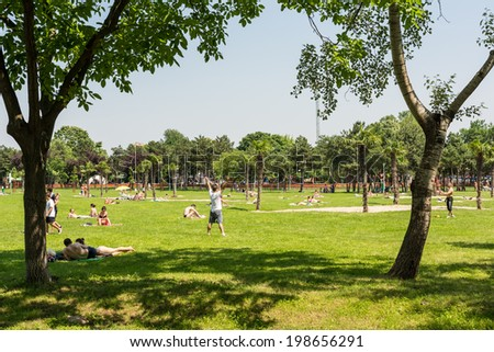 BUCHAREST, ROMANIA - JUNE 08, 2014: People Having Picnic And Playing Games In Public Park On Summer Day.