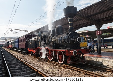 BUCHAREST, ROMANIA - JUNE 11, 2014: Vintage old train with a steam locomotive who is preparing for a short trip. Gara de Nord, Bucharest, in June 2014 - stock photo