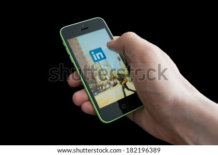 BUCHAREST, ROMANIA - MARCH 17, 2014: Photo of a hand using linkedIn app on iphone 5C. LinkedIn becomes more and more used by Romanian employers. - stock photo
