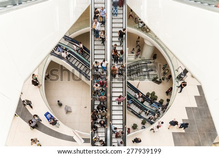 BUCHAREST, ROMANIA - MAY 14, 2015: People Crowd On Escalators In Luxury Shopping Mall. - stock photo