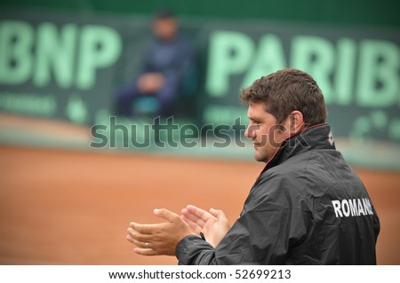 BUCHAREST, ROMANIA - MAY 9: Romania's second coach Gabriel Trifu is encouraging the players during the Davis Cup meeting between Romania and Ukraine at the BNR Arenas on May 9, 2010 in Bucharest, Romania. - stock photo