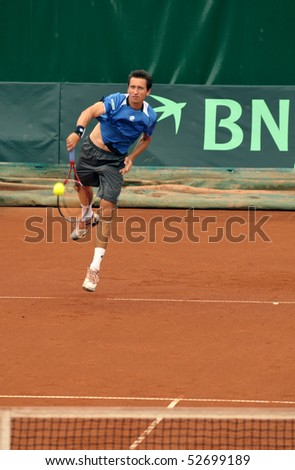 BUCHAREST, ROMANIA - MAY 9: Ukraine's Sergiy Stakhovsky is performing a serve during the forth match of the Davis Cup meeting between Romania and Ukraine at the BNR Arenas on May 9, 2010 in Bucharest, Romania. - stock photo