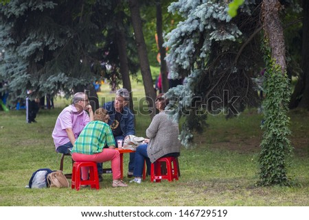 BUCHAREST, ROMANIA - MAY 17: Unidentified group of people  gather and relax in the park during the celebratory event Turkish Festival on May 17, 2013 in Bucharest, Romania. - stock photo