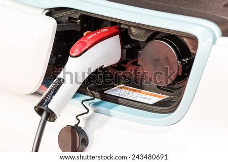 BUCHAREST, ROMANIA - OCTOBER 31, 2014: Kia Soul EV Electric Car Charge At Power Supply. Soul EV is an all-electric all new compact car manufactured by Kia Motors for the first time in 2014. - stock photo