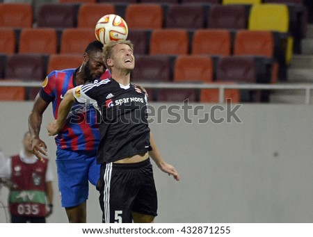 BUCHAREST, ROMANIA - SEPTEMBER 18, 2014: Fernando Varela and Kenneth Emil Petersen pictured during the UEFA Europa League game between Steaua Bucuresti and Aalborg on National Arena. - stock photo
