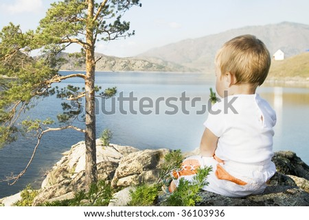 Buchtarma. Nature of the Eastern Kazakhstan. Child seated on the shores of  Inlet.