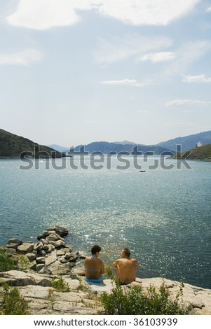 Buchtarma. Nature of the Eastern Kazakhstan. Man and woman seated on the shores of Lake and  talking