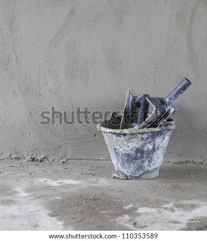 bucket and a trowel on a wall background - stock photo