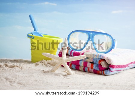 Bucket and shovel on the beach with a starfish and snorkel mask - stock photo