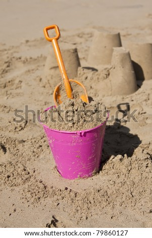 Bucket and spade in sand on the beach in sunlight - stock photo
