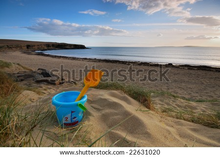 Bucket and spade on beach - stock photo
