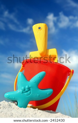 Bucket and spade on tropical beach with blue sky
