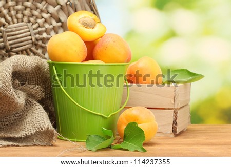 bucket and wooden box with ripe apricots on wooden table on green background
